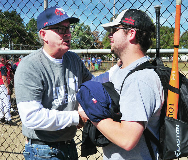 Event organizer/sponsor Mark Reedy, left, greets one of the many players who took part in the 3rd annual Battle of the Badges at Mote Park in Piqua last Saturday.