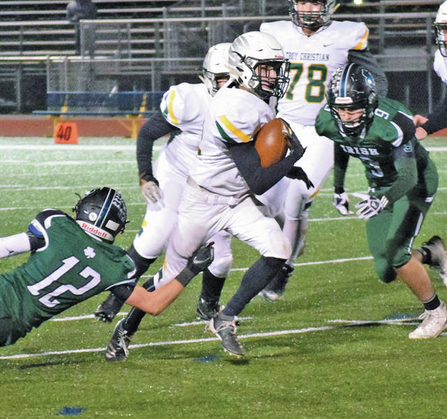 Photo courtesy Steve Helwagen Troy Christian's Nathan Waltz runs between a pair of Fisher Catholic defenders Friday night.