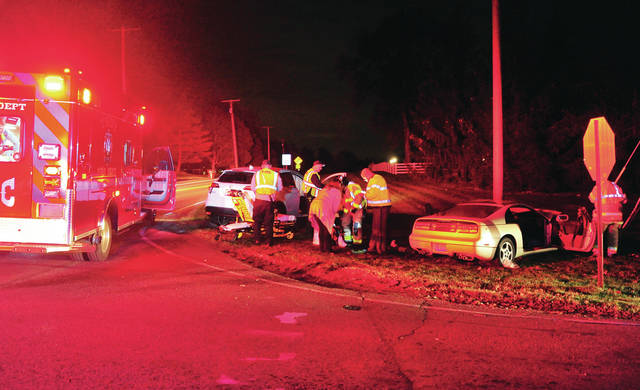 Troy Fire Department medics tend to victims of a crash at the intersection of Peters and Swailes roads on Wednesday evening.