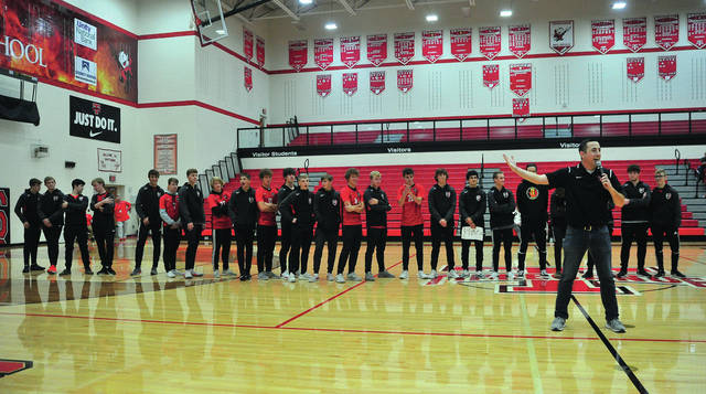 Tippecanoe High School teacher Luke Zerkle, right, gives cheering tips to the student body during a pep rally on Friday for the Tippecanoe Boys Soccer Team as they prepare to play for an OHSAA state soccer title on Sunday in Columbus.
