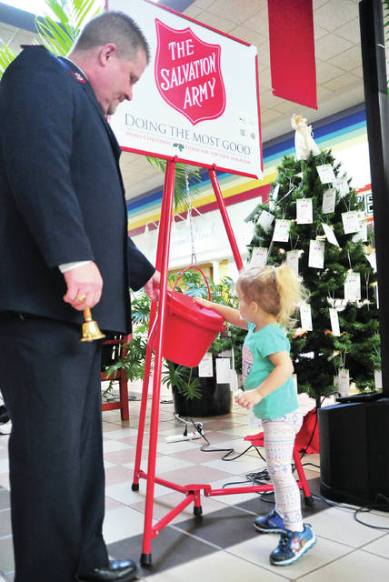 Hope Cooper, 2, of Piqua drops the first donation of the season into the Salvation Army kettle at the Miami Valley Centre Mall on Thursday as Major Robert Kramer looks on during the annual SA kickoff event at the mall.
