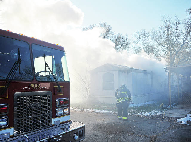 Firefighters from Piqua, Lockington, and Fletcher battle a mobile home fire at the Paris Court mobile Home Park on N. Co. Rd. 25-A on Friday afternoon.
