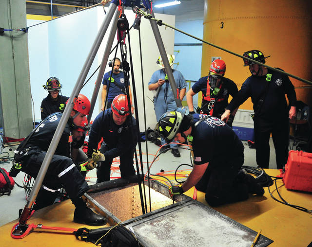 Piqua firefighters work on confined space rescue techniques during a training day on Thursday at the former Piqua Water Treatment facility.