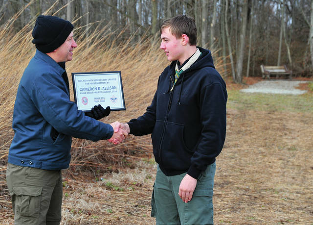 Miami County Park District Executive Director Scott Myers presents a certificate to Troy Jr. High student Cameron Allison of Troy at the Wannemacher Nature Reserve on Sunday. Allison created a new hiking trail through the reserve as his Eagle Scout project. He is a member of Troy Troop 365.