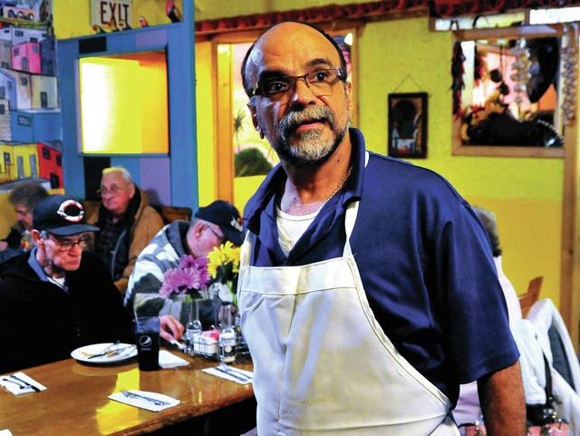 Rueben Pelayo, owner of El Sombrero restaurant in Troy, assists guests to their seats on Thanksgiving Day. Thursday marked the 25th year that Pelayo, his family, and a group of dedicated volunteers have served Thanksgiving dinner to thousands of diners from around the area.