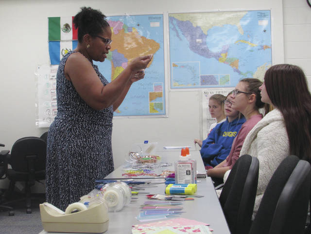 Sam Wildow | Miami Valley Sunday News Demetria Woods (left) of Miami County's OSU Extension Office teaches students how to use to create an electronic circuit and light miniature LED lights during Edison State Community College's Women in STEMM Expo on Friday.