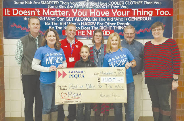 Betsey Johns and Brayden Myers accept an Awesome Piqua grant check from members.