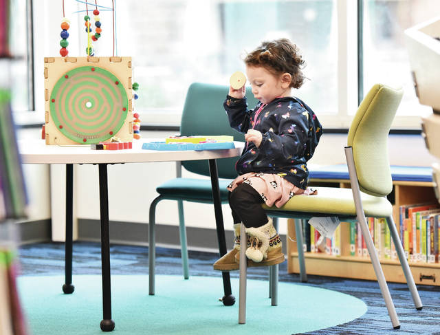 Eevee Hoskins, 1, of Piqua, daughter of Joshua Hoskins and Kylsey Abbott, works on a puzzle at the Amos Memorial Public Library Friday, Nov. 22. Eevee stopped by the library with her grandma, Tracey Wood, after Wood got done with a visit to Wilson Health.