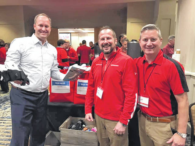 Provided photo From left to right, State Farm agents Nathan Baker of Dayton, Zack Jacobs of Tipp City, and Jeff Mundy of Middletown help lead a sock collection drive for Shoes 4 the Shoeless.