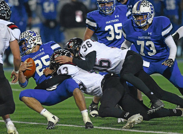 Ben Robinson|GoBuccs.com Covington's Gavin Swank (43) and Connor Sindelir (36) takle Chillicothe Southeastern quarterback Lane Ruby Friday night in the D-VI regional semifinal at Xenia High School.