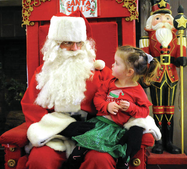"""Lilian Swan, 2, of Piqua isn't quite sure what to think about the """"Jolly old Elf""""as she size up Santa at the Piqua Public Library on Saturday."""