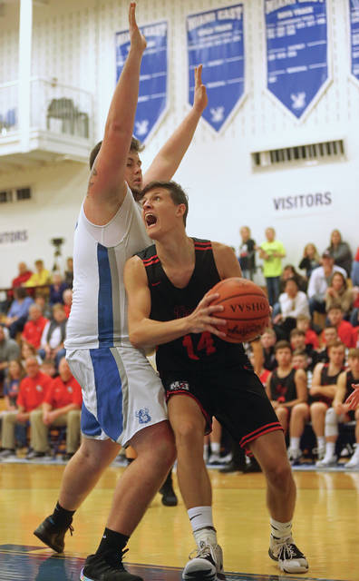 Lee Woolery | Miami Valley Today Milton-Union's Brandon Lavy drives to the basket as Miami East Keegan Mahaney defends Saturday at Miami East High School.