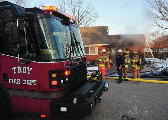 Troy firefighters battle a house fire on Sheridan Court on Friday morning.