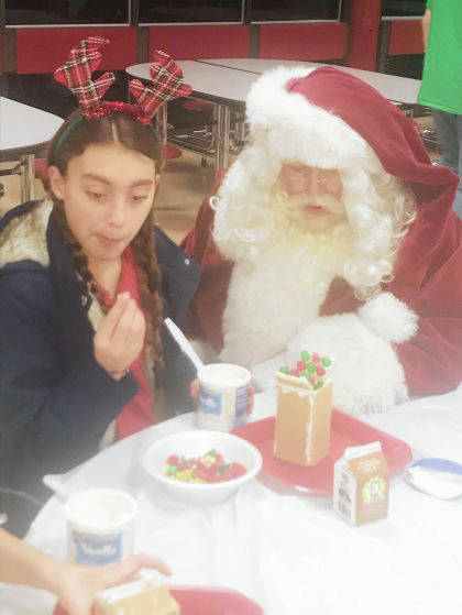 Provided photo Santa Claus, right, gives Deanna Rohlfs building tips Wednesday at Troy Junior High School during The Future Begins Today Club's Gingerbread House Night.