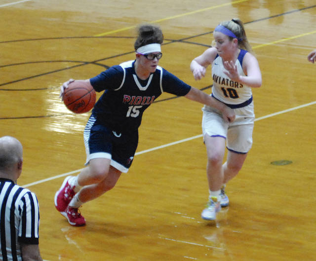 Rob Kiser|Miami Valley Today Piqua's Karley Johns fends off Butler's Gracie Price as she heads towards the basket.
