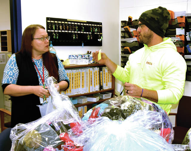 Lougena Martinez, administrative assistant to the transportation supervisor for Piqua City Schools, left, and Ben Gover from the City of Piqua, sort coats, hats, and gloves at Piqua High School on Friday as the donations were being delivered to the school's transportation department.