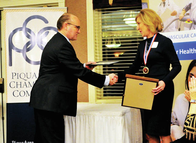 Piqua Area Chamber of Commerce board president for 2020 Rick Hanes congratulates Order of George recipient Mimi Crawford during Thursday's annual chamber dinner at the Piqua Country Club.