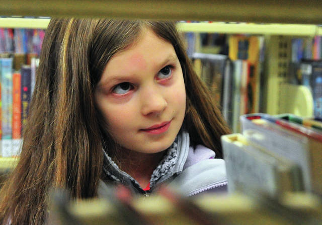 Sydney Pacher, 9, of Troy, searches for a book at the Troy-Miami Coynty Public Library on Tuesday afternoon.