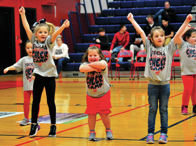 Piper Stillwell, Olivia Abney, and Emma Bowers, l-r, show their spirit as they perform with the Piqua Cheer Camp cheerleaders during last Friday's boys basketball game against Tippecanoe at Garbry Gym.