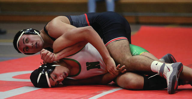 Lee Woolery   Miami Valley Today Troy senior Carlos Quintero controls Northmont's James Wilson during the Trojans' Senior Night dual Tuesday at Troy High School.