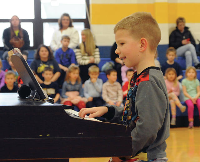 "Piqua Catholic School first grade student Landon Woehrmyer performs a piano solo during Friday's talent show at the school. Friday was also ""mismatch day"" for students. These were just two of many activities taking place during Catholic Schools Week."