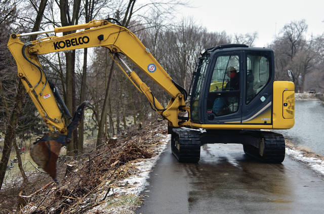 Work crews continue to clear the bike path hillside along the Hydraulic Canal above Forest Hill Cemetery in Piqua, in spite of colder temperatures, sleet, and snow.