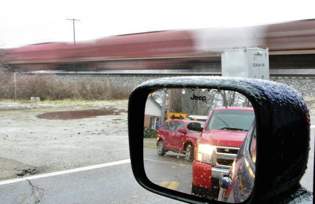 A train makes its way north out of Troy on blustery Thursday as cars wait at the Eldean Road railroad crossing.