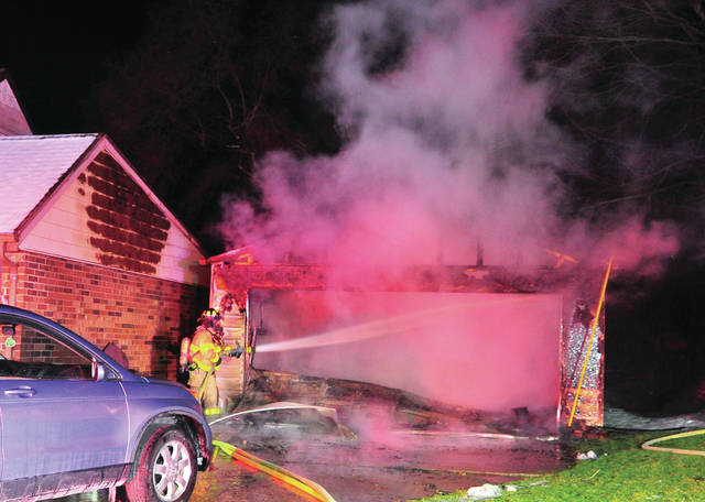 Troy firefighters battle a garage fire on Bunker Hill Drive on Saturday evening.