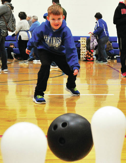 Miami East Elementary first-grader Andy Fraley looks for a strike as he tries his hand at bowling during last Saturday's annual Viking Fest fundraising event at the school.