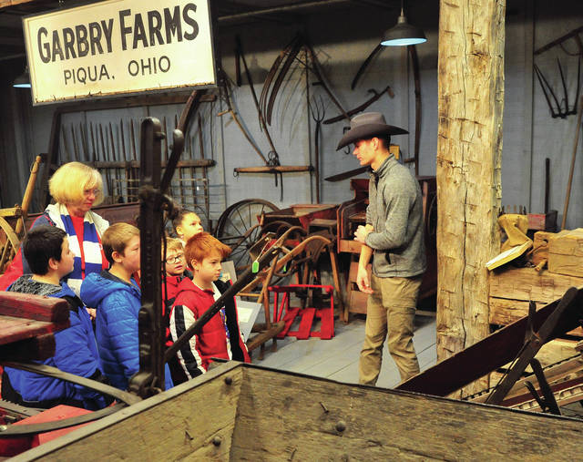 Fletcher Metz of Covington, a senior at Upper Valley Career Center Environmental Occupations program teaches a group pf Springcreek Elementary students about antique farm tools and machinery during a tour of the Garbry Museum at Willowbrook on Wednesday.