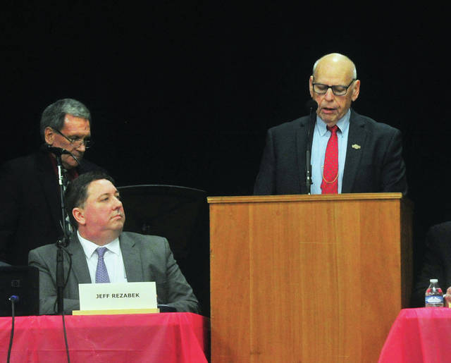 Miami County Commissioner Greg Simmons, right, speaks during Meet the Candidates Night at Troy Junior High on Wednesday, as Jeff Rezabek, candidate for judge in the 2nd District Court of Appeals, seated, looks on.