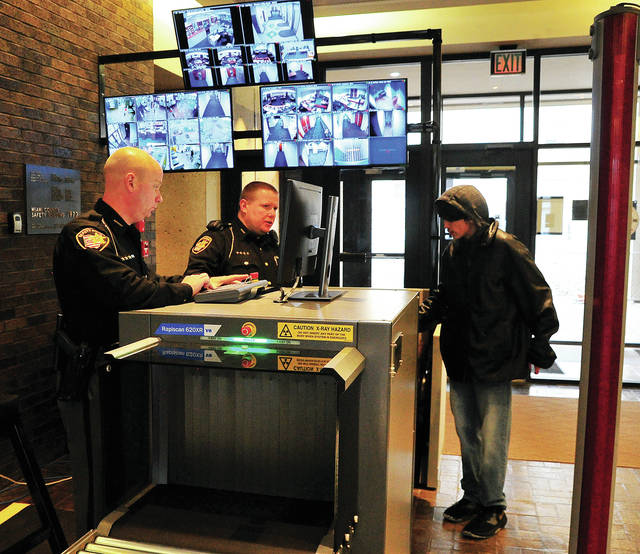 Deputies Andy Walker and Tim Larger of the Miami Co. Sheriff's Office check the bag of a person entering the Miami County Safety Building earlier this week. Beginning Monday, March 2, everyone entering the Safety Building will have their bags checked by the scanner and pass through a metal detector before they are admitted to the building. Rules for what may, and may not, be brought in are similar to TSA rules at an airport. The monitors above the station allow deputies to monitor courtrooms, offices, and hallways throughout the building. A similar station will begin operation in the Courthouse in the near future. In addition, the east doors to the Safety Building will not be open to the public. All persons entering the building must to do through e west doors (courthouse side).