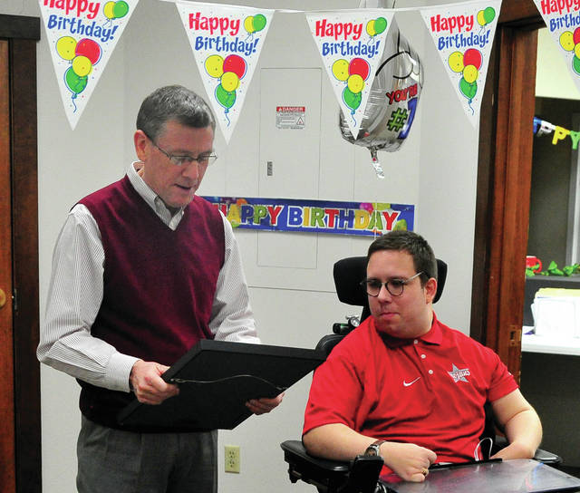 Troy Service and Safety Director Pat Titterington, left, reads a proclamation from Troy Mayor Robin Oda, proclaiming Thursday, March 12, to be Michael Ham Day, in celebration of Ham's 30th birthday. The Planning and Zoning employee, known as Mr. Troy received more than 100 birthday cards from fellow employees.