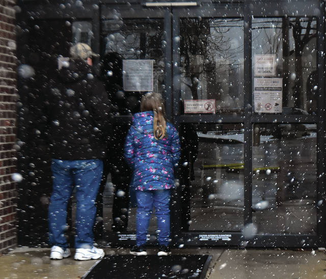 A father and daughter arrive at the Troy-Miami County Public Library on Saturday afternoon to find it closed due to the coronavirus situation.