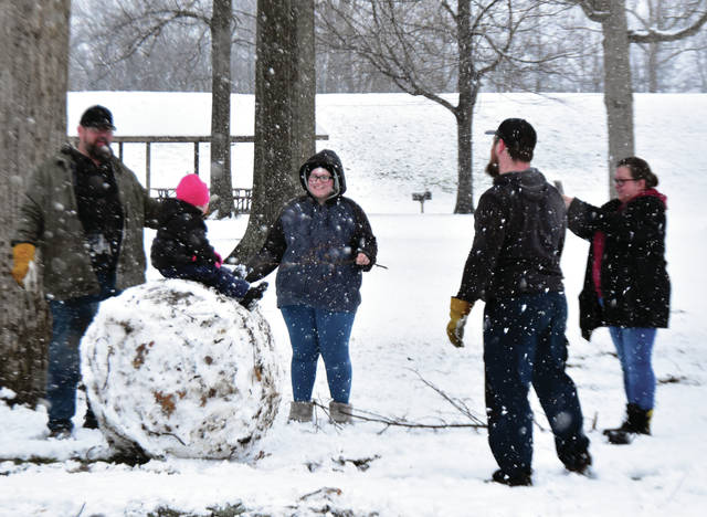 The Burke and May families of Troy build a snowman at the Troy Community Park on Saturday afternoon. The family includes Devon Burke, his daughter Devon, and wife Jessica, along with grandparents Jim and Julie May.