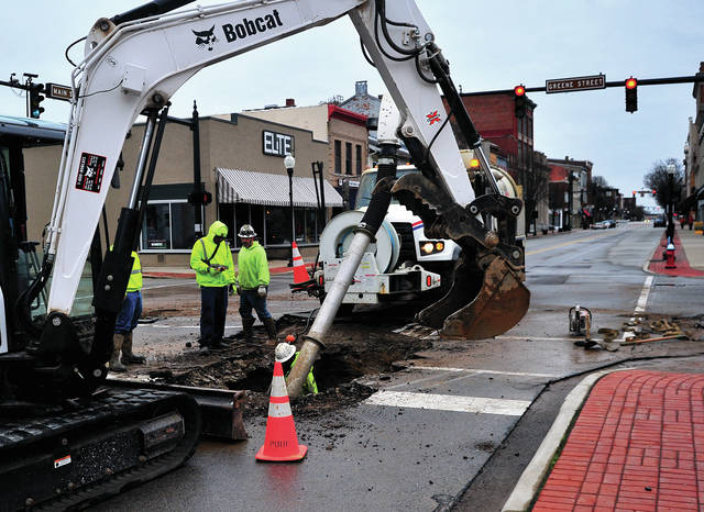 Piqua crews work to repair a broken water main at the intersection of North Main and Greene Streets on Monday morning.