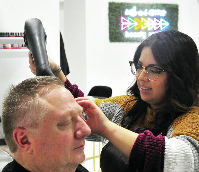 Stylist Claudia Kushinski of Troy blow dries customer Bob Peoppelman, also of Troy, at Oak and Arrow Beauty Room on Wednesday evening, shortly before state-mandated closures take effect due to the current COVID-19 situation.