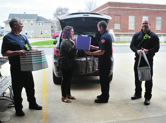 Lindsay Taylor of Oak and Arrow Beauty Room in Troy unloads more than 36 boxes of donated sanitary gloves and masks at Troy Fire Department Station 1 on Tuesday. Assisting with the unloading are Troy Firefighters Stave Schmitz, Don Pemberton, and Andrew Bates.