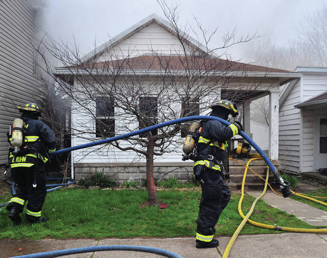 Firefighters move water lines as they battle a house fire in the 600 block of South Wayne Street in Piqua on Tuesday afternoon.