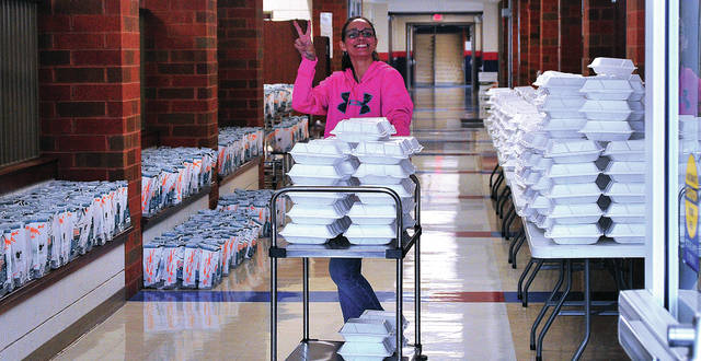 Piqua City Schools employee Tara Hall is all smiles as she and a number of her co-workers volunteer to prepare and distribute 800 hot lunches and 800 breakfasts to Piqua City Schools students on Monday. In addition to the 1600 meals distributed curbside at PCIS, another 1200 meals were handed out at Piqua High School.