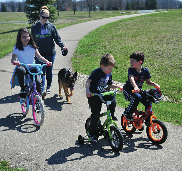Ashley Miramontes of Troy walks the bike paths at Duke Park in Troy while her kids Cameron, 3, Audrine, 10, and Mason, 4, ride their bikes.