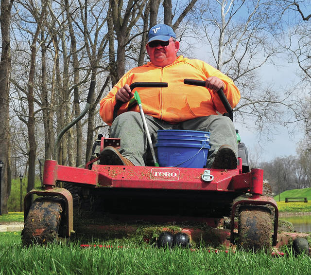 Retired Miami East teacher and coach Kevin Pyers cuts grass at Treasure Island Park on Wednesday. City and county parks personnel are shifting into high gear to keep up with growing grass.