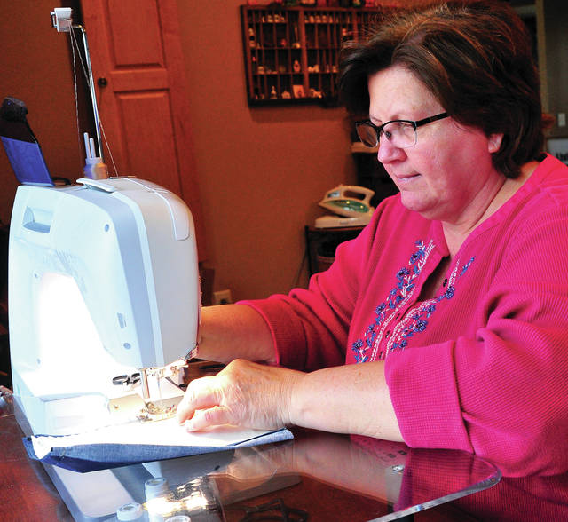 Cindy Lillicrap of Piqua sews protective masks in her home shop on Thursday. Lillicrap decided that she needed to do what she could to help fulfill the shortage of protective gear. She has completed more than 700 masks and has orders for more than 300 additional. Her masks have been been purchased by workers from a number of area medical professionals.