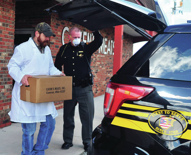 Clay Caven of Caven's Meets in Conover loads a case of frozen meat into Miami County Sheriff's Office Captain Tom Wheeler's cruiser on Thursday. Caven's donated two cases of meat to the Miami County Sheriff's Office who will, in turn, deliver the meat to New Path Food Pantry for distribution to those in need.