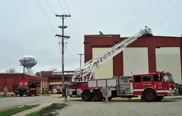 Firefighters from Troy and Tipp City Fire Departments work at the scene of a reported fire at Troy Laminating & Coating on South Union Street on Monday morning.