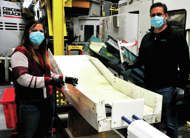 Alicia Olivera, left, pulls a part off the press that will be a component of a protective face shield at Evenflo in Piqua on Wednesday as Joe Calabrese, vice president of Operations for Evenflo, displays a prototype of the finished product.