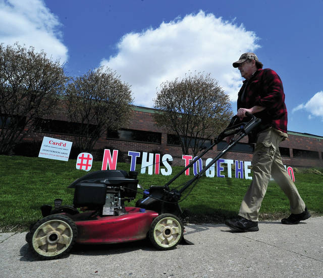 Don Lauber of Troy finishes mowing the grass at the Troy Miami County Public Library on Thursday as the sign behind him reminds all of our efforts to get through the COVID-19 situation and get Ohio back to work. Lauber is a retired USPS employee who now works part time at the library.