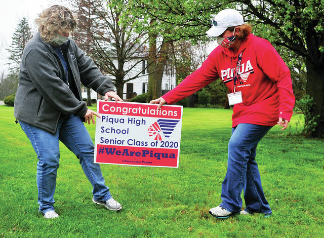 Piqua City Schools administrative staff members Theresa Anderson, left, and Mindy Gearhart place a sign in the front yard of a Piqua High School Class of 2020 senior on Wednesday morning. More than 20 teachers, administrators, and family members met at Piqua Junior High School to pick up and deliver signs to more than 240 Piqua High School seniors.