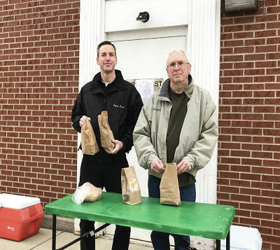 """FBC lead pastor the Rev. Frank Rupnik and member Steve Pettit hand out food as part of the church's program, called """"The Breakfast Club."""""""