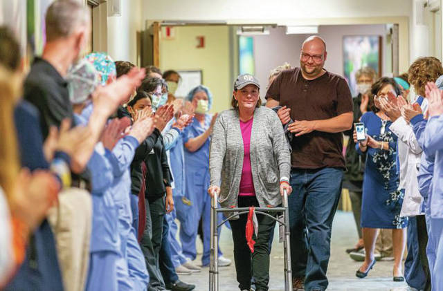 "Amy De Vos, center, alongside her husband Thomas, is given a ""clap out"" by Upper Valley Medical Center staff recently in celebration of her release from the hospital after a stay of 29 days, 16 of which De Vos, a respiratory therapist herself, spent on a ventilator fighting for her life."